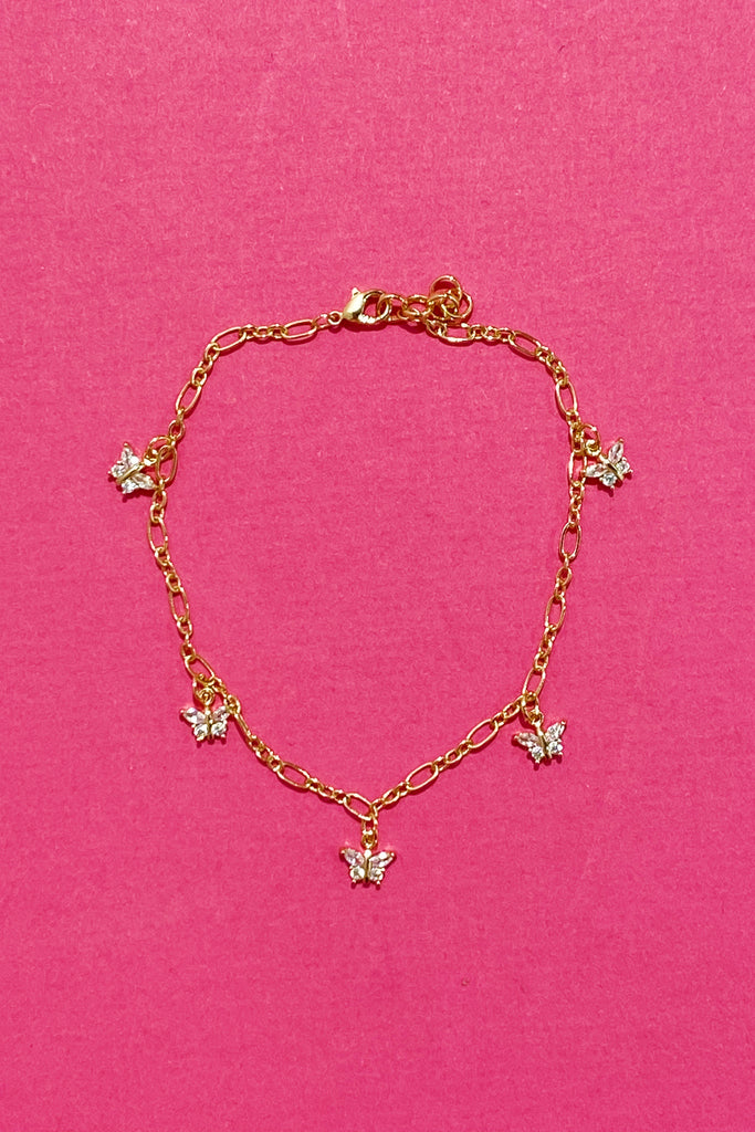 The butterfly row anklet on a hot pink background. Shows the thicker gold chain and jewel butterflies spread evenly throughout the anklet.