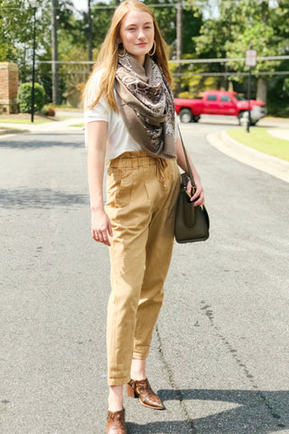 Model wearing taupe snake skin print scarf from online Boutique Ellison + Young