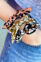 Woman wearing three leopard print scrunchies on her wrist in olive, rust, and black
