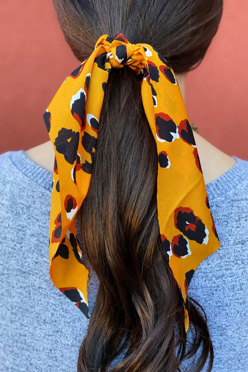 Woman wearing orange leopard print scarf scrunchie