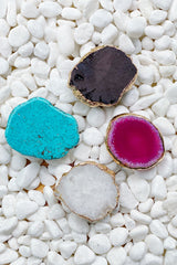 Beauty of Nature Stone Phone Grips on a white rocky surface. The white druzy, black druzy, pink agate, and turquoise are shown in the photo.