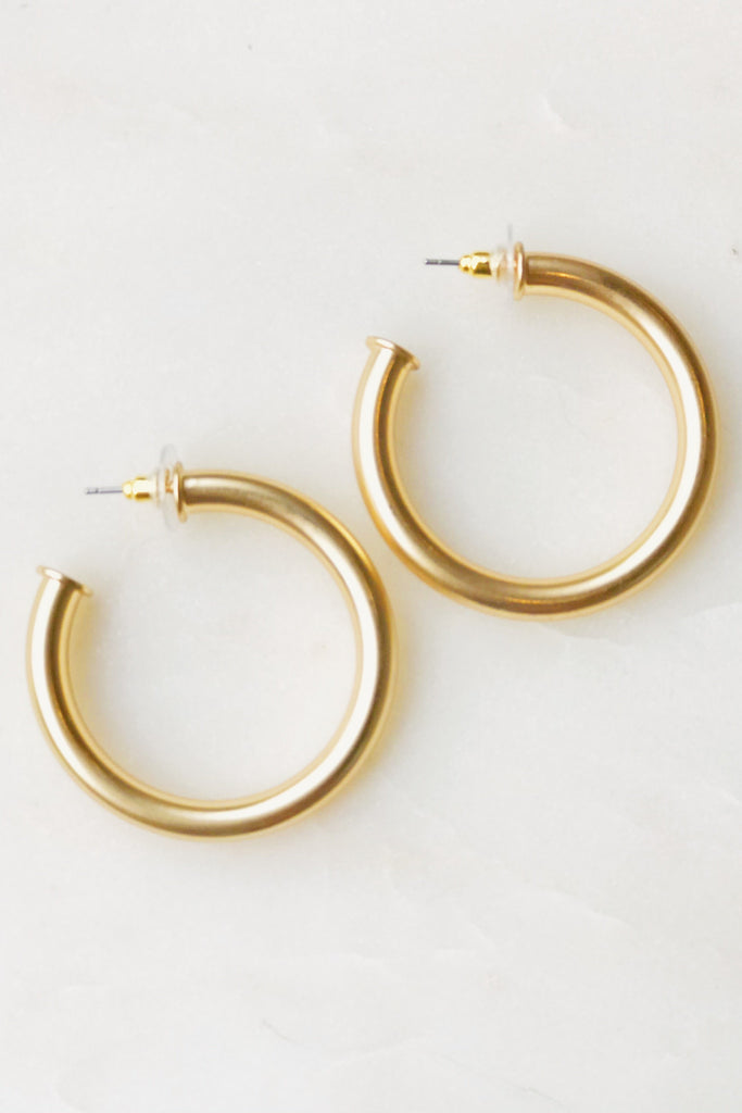 Gold tube hoop earrings displayed on white background