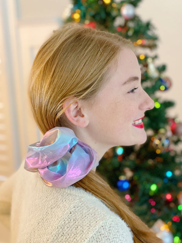 Woman with red hair wearing a pink hologram silk scrunchie in her side ponytail