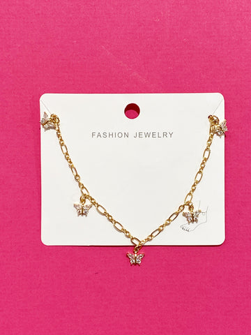 The butterfly row anklet in its packaging on a hot pink background.