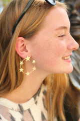 red hair woman wearing gold hoop earrings with star details