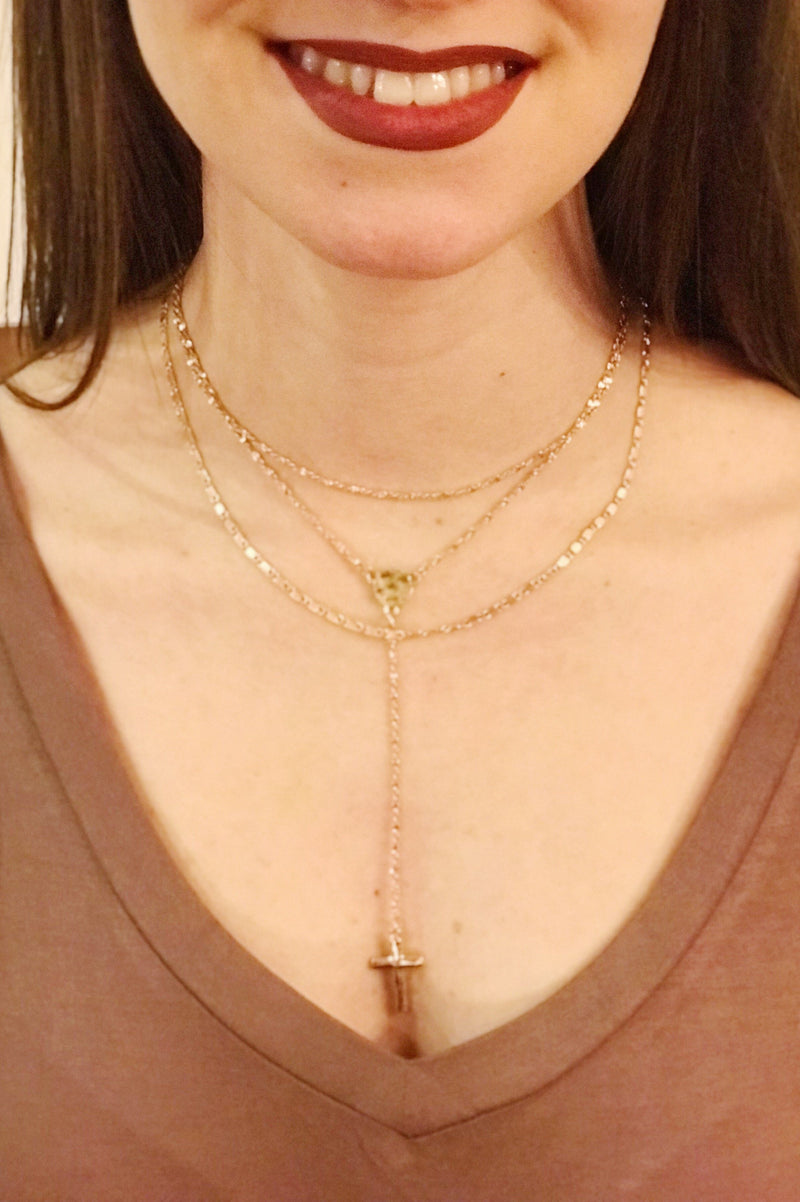 Woman wearing Gold triple layered necklace with cross drop pendant