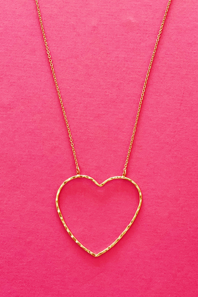 Big Heart to Love, Gold necklace shown on a hot pink background.