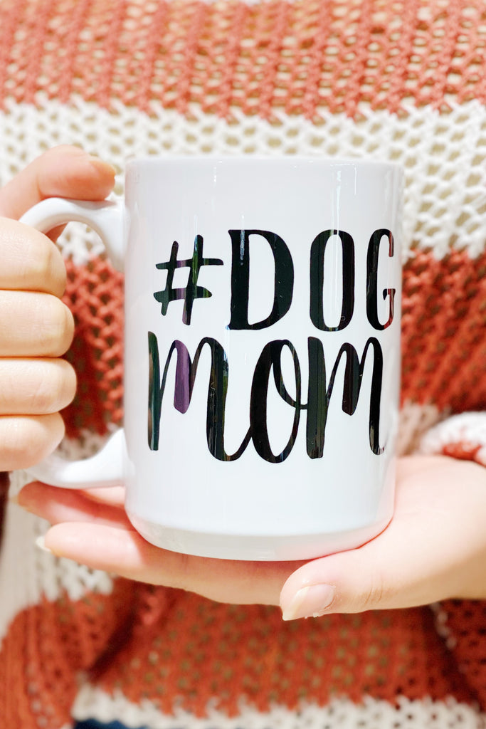 White coffee mug that says #Dog Mom in black text on front of the mug.