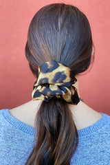 Brown haired woman wearing giant leopard print scrunchie around her low ponytail