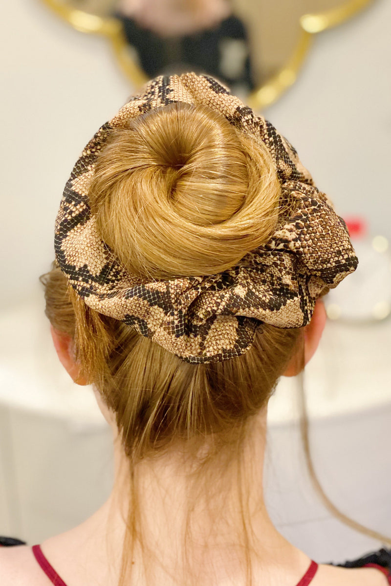 Woman with red hair wearing a snake skin silk scrunchie in her bun