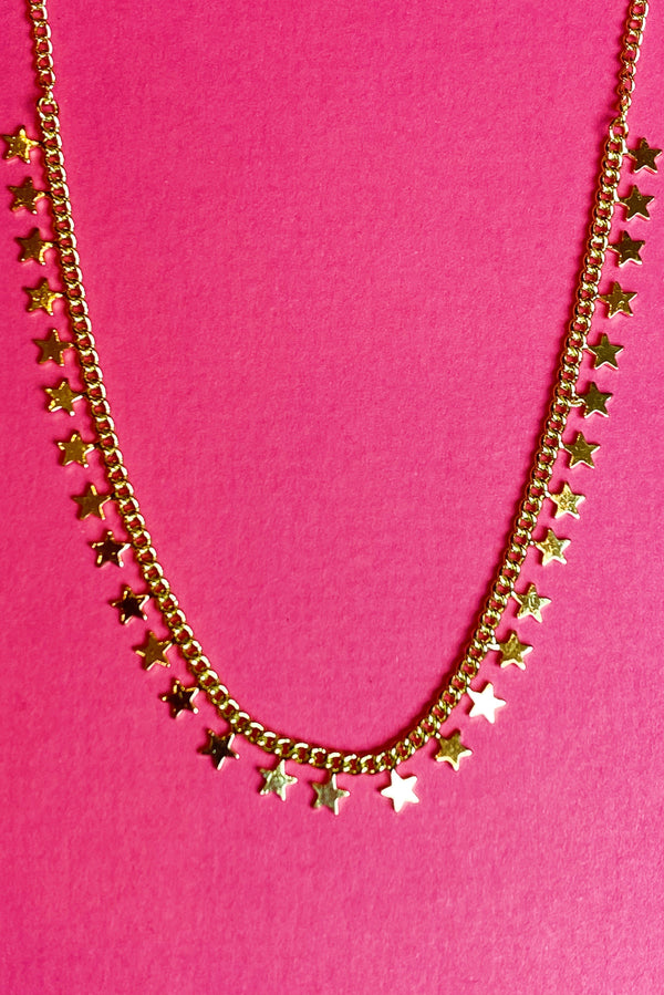 A chained Twinkling Star Necklace on a hot pink background displaying the gold color and close details.