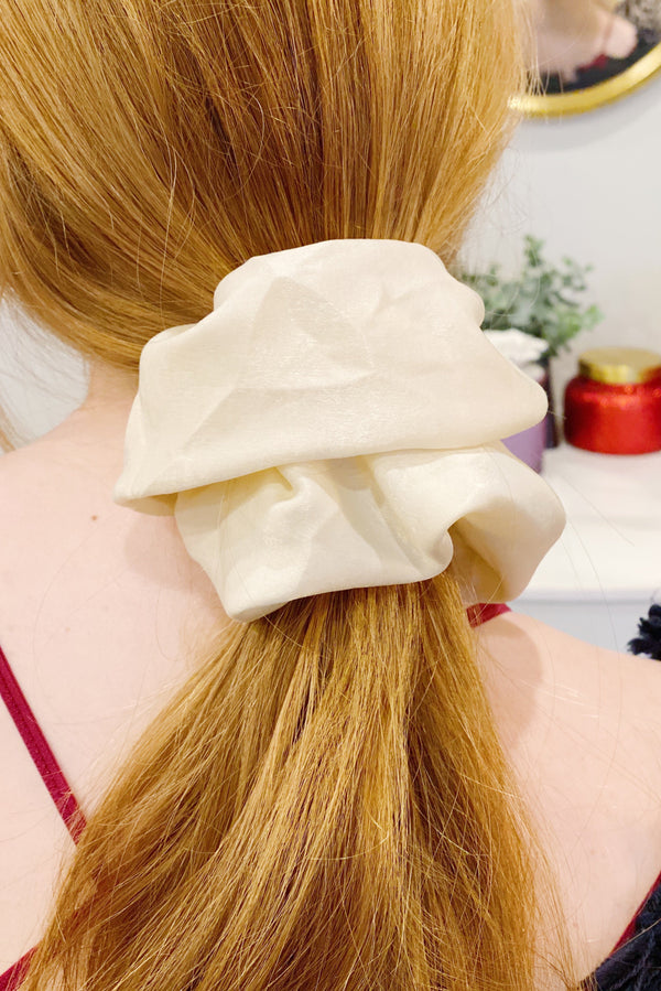 Woman with red hair wearing a ivory silk scrunchie in her ponytail