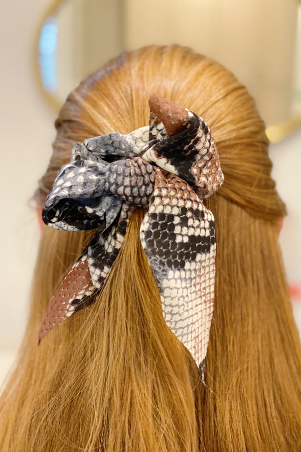 Red headed woman wearing snake skin ponytail scrunchie in a bow in her half up half down hair style