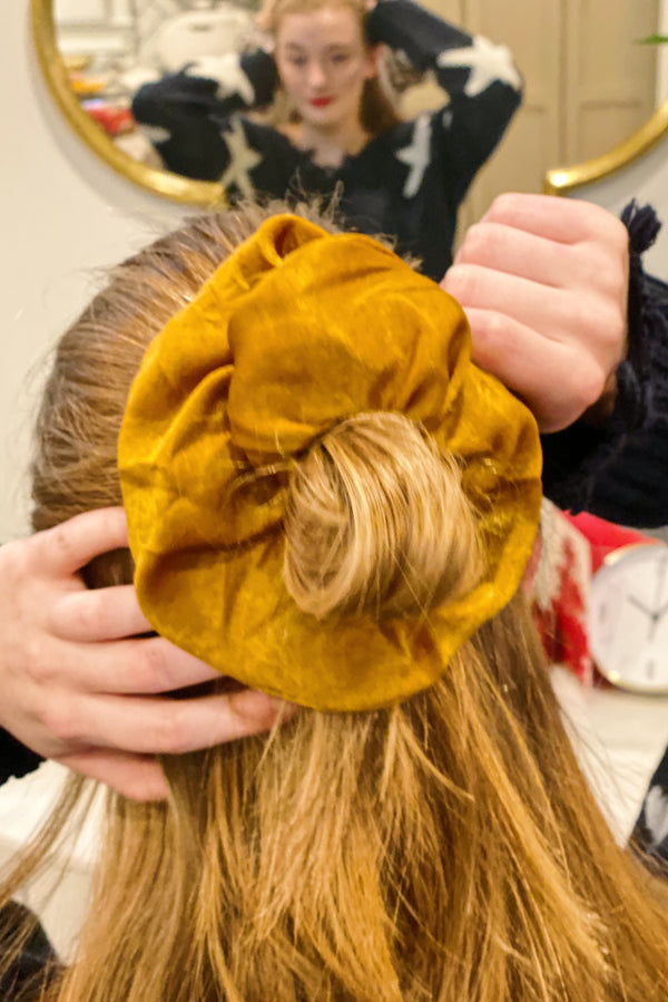 Woman with red hair wearing a rust silk scrunchie in her half up half down ponytail