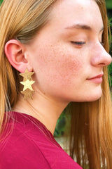 Red hair woman wearing gold star dangling earrings