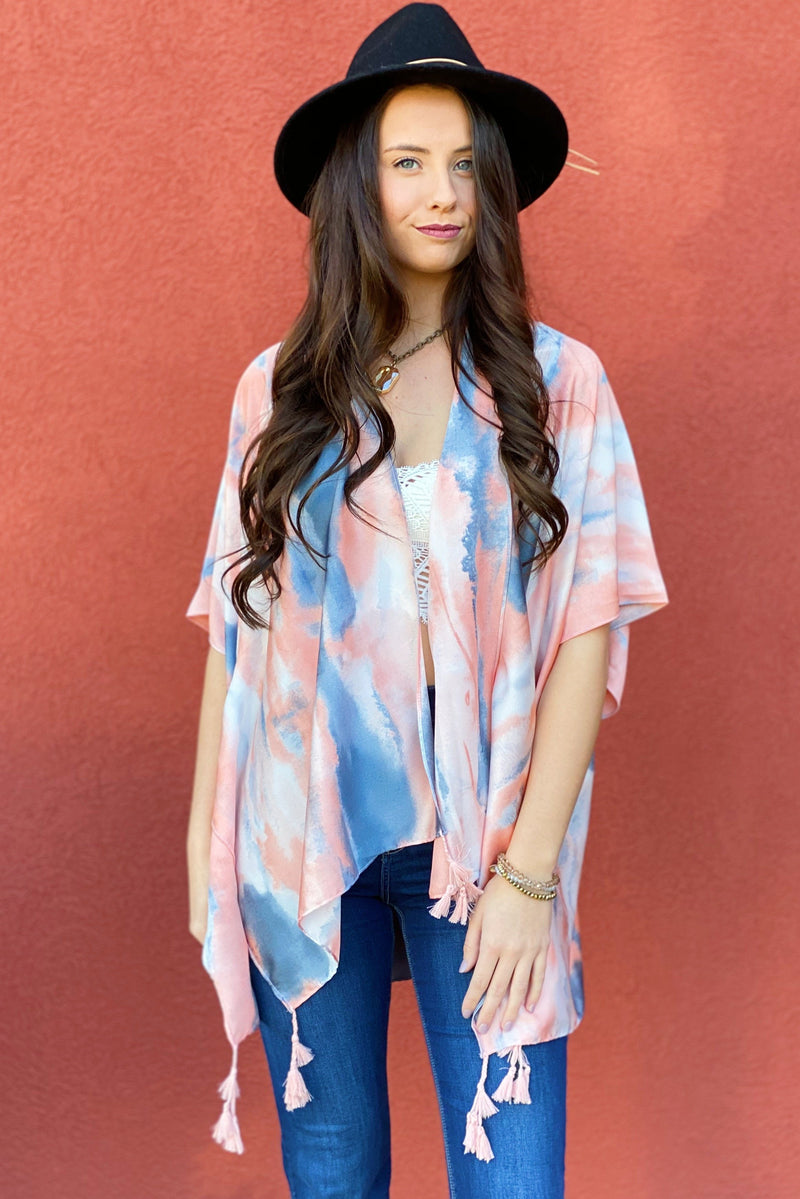 Model wearing the Bright Skies Tie Dye Kimono in Pink showing the front of the kimono and the tassels on the bottom of the kimono