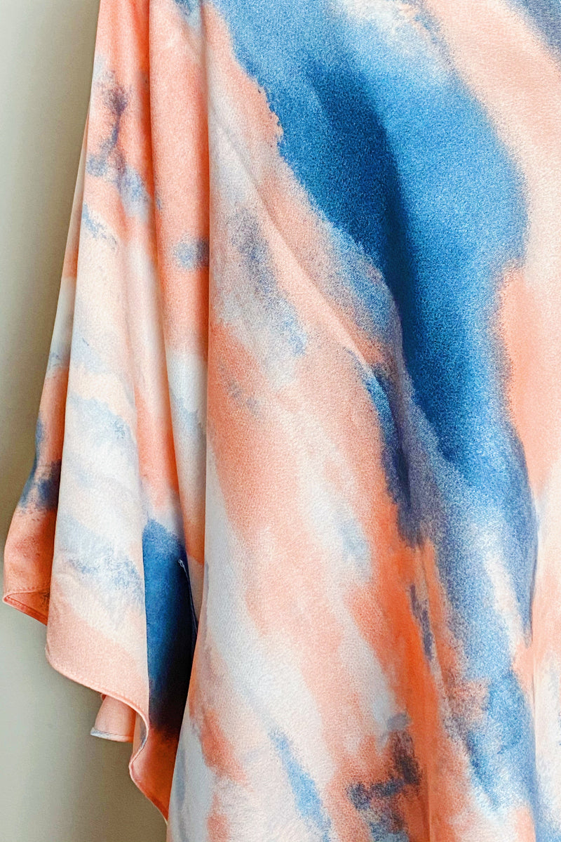 A close up view of the pinks and blue colors and texture of the fabric of the Bright Skies Tie Dye Kimono in Pink