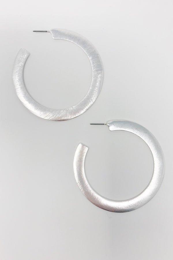 Thick flattened metal silver hoop earrings displayed on white background