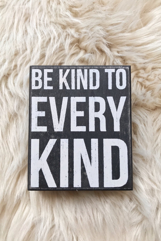 "Box sign, every kind on a fur carpet. Th3 sign states, ""Be kind to Every Kind"""
