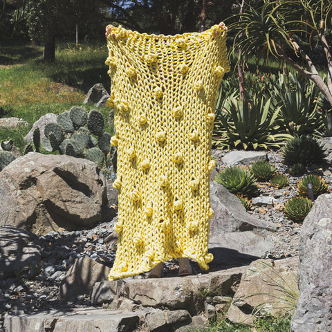 Create this chunky arm knitted blanket. We used chunky wool merino bumps of Plump & Co 2 ply yellow yarn, with Giant 45mm Needles from Plump & Co. In New Zealand and Australia. With chunky wool merino knits and layers of textures for your home inspiration.
