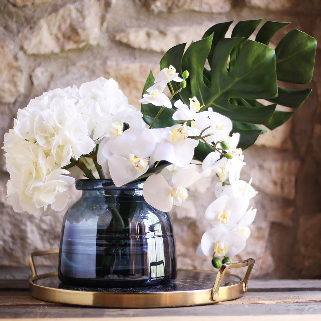 Real Touch White Orchid, Hydrangea & Monstera Leaf Floral Arrangement in Smokey Blue Glass Jug
