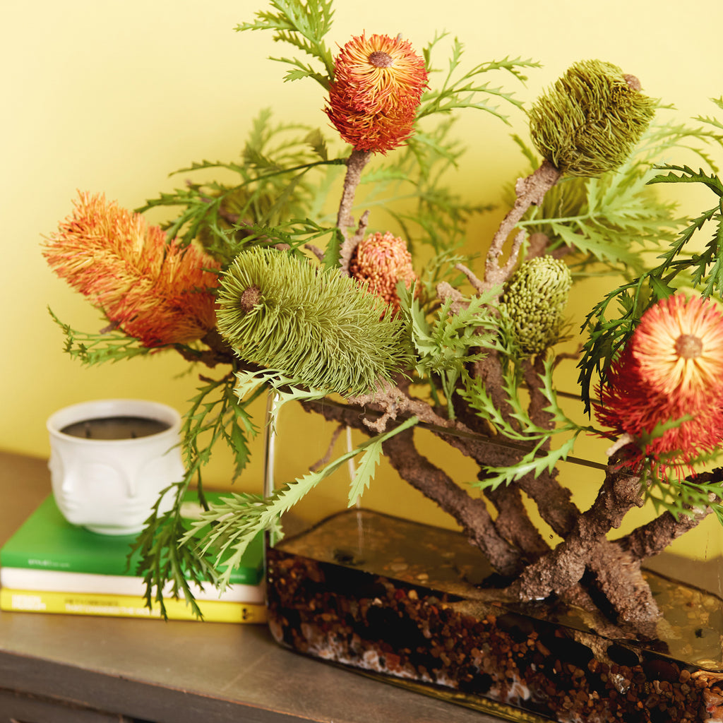 Orange and Green Banksia Branch Floral Arrangement in Large Glass Terrarium with River Rocks and White Sand