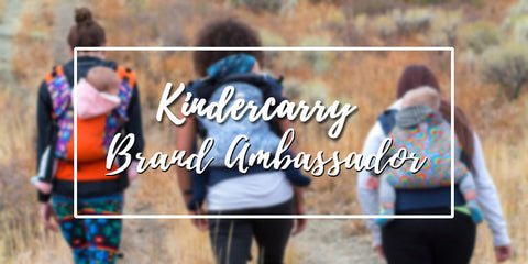 A blurred image of mom's hiking while carrying their babies on their back with a Kinderpack carrier. A text box with an outline says Kindercarry Brand Ambassadors