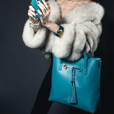 Close up of a model wearing Charlotte Tote - Caribbean Blue Leather Handbag by Cristina Sabatini