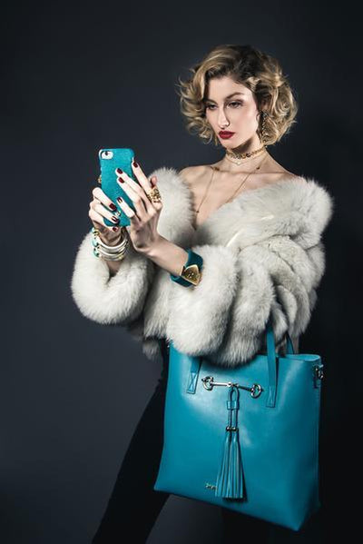 Woman Wearing Charlotte Tote - Caribbean Blue Leather Handbag by Cristina Sabatini