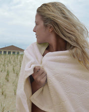 Girl on beach wrapped in Affina Hexo Bath Towel