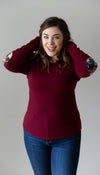 cranberry lightweight sweater with floral faux leather elbow patches, hem is lower at the back, long sleeves, made in canada