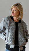 quilted bomber jacket, light grey, black ribbing detail, pockets and metal zipper