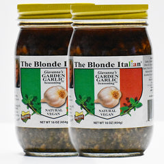 Image of two jars of The Blonde Italian brand's Giavanna's Garden Garlic Seasoning. This is a delicious blend of garlic and herbs in oil that can be added to any recipe to add big flavor fast. The jars show The Blonde Italian name on the label. The lids of the jars are yellow.