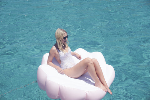 Kololo Pink Seashell floaty girl wearing sunglasses lounging in the ocean looking to the side