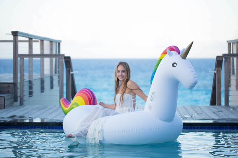 Kololo Giant Unicorn rainbow floaty girl sitting sideways smiling