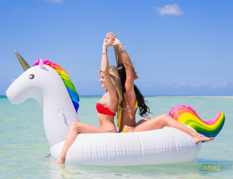 Kololo Giant Unicorn rainbow floaty two girls sitting backs to each other holding hands under the sun