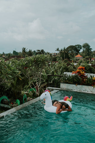 Kololo Big Unicorn rainbow floaty girl lounging infinity pool