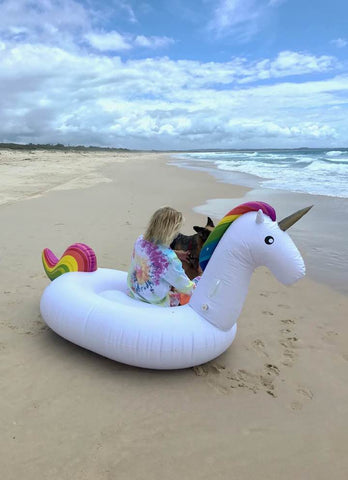 Kololo Giant Unicorn rainbow floaty guy sitting with dog at the beach