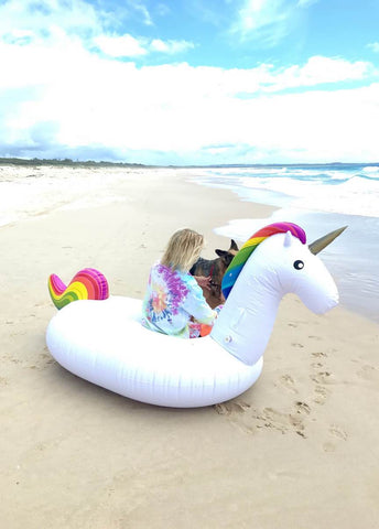 Kololo Giant Unicorn rainbow floaty guy sitting back turned