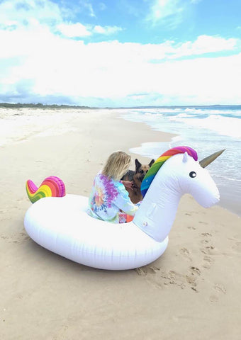 Kololo Giant Unicorn rainbow floaty guy sitting back turned with dog