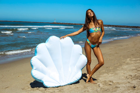 KOLOLO Blue Seashell floaty girl at the beach standing next to floaty