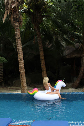 Kololo Big Unicorn rainbow floaty girl in white swimsuit back turned