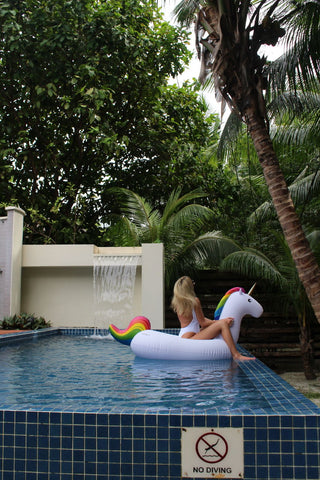 Kololo Big Unicorn rainbow floaty girl sitting pool view
