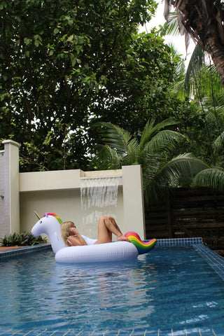 Kololo Big Unicorn rainbow floaty girl lounging wearing sunglasses