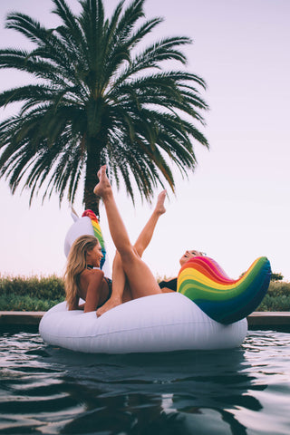 Kololo Giant Unicorn rainbow floaty two girls lounging with legs up