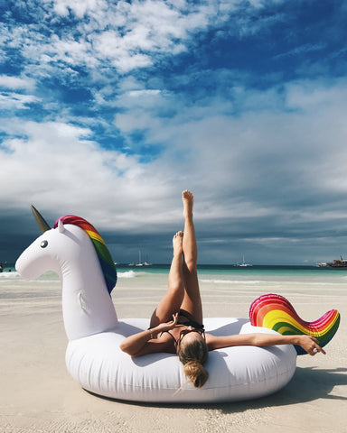 Kololo Giant Unicorn rainbow floaty girl lounging at the shore legs raised