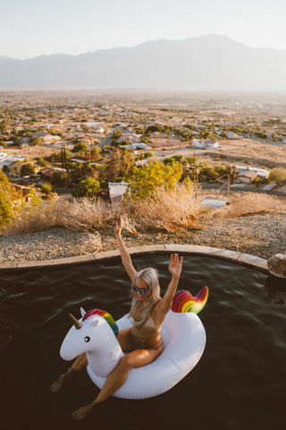 Kololo Big Unicorn rainbow floaty birds eye view with girl sitting on the floaty with desert background