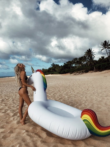 Kololo Giant Unicorn rainbow floaty girl at the beach holding unicorn head thrown back and smiling