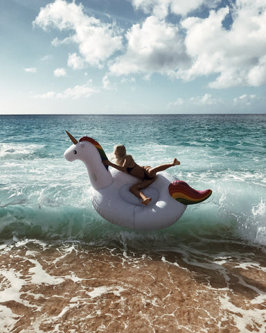 Kololo Giant Unicorn rainbow floaty girl sitting on the unicorn with waves wipeout