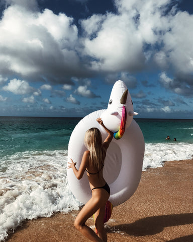 Kololo Giant Unicorn rainbow floaty girl holding unicorn walking towards the beach